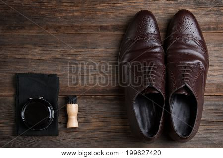 Classic men's shoes brown with shoe cream on a wooden background. Shoe care.