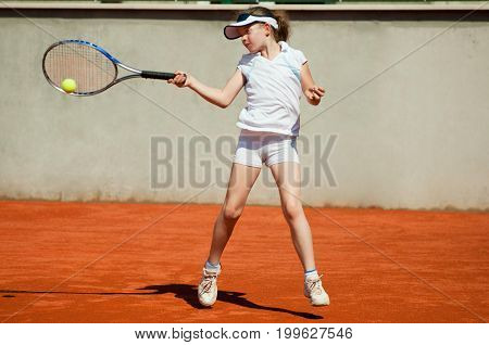 Young Girl Hitting The Ball With Backhand Slice, Color Image, Outdoors