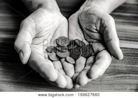 Euro coins in hand of senior. Black and white conceptual photography