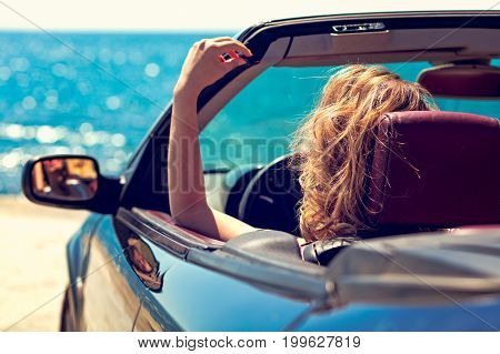 Beautiful blond smiling young woman in convertible top automobile looking sideways while parked near ocean waterfront.