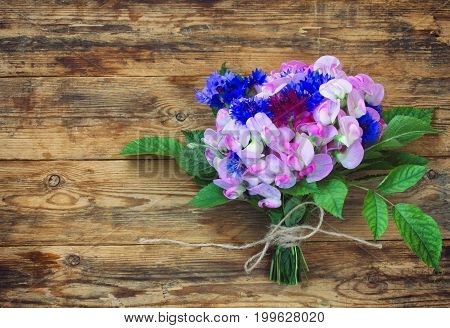 Summer fragrant bouquet of cornflowers and sweet peas on wooden table retro wedding style congratulations for holiday free space