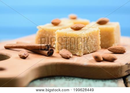 Halava Indian flour sweetmeats cut in squares decorated with almonds on wooden board side view closeup