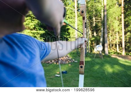 Mature Athlete Aiming Arrow At Target Board In Forest