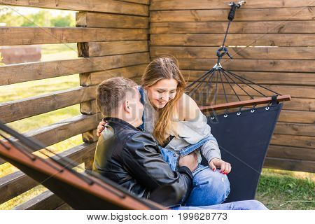 happy pregnant couple sitting in hammock - family, parenthood and happiness concept.