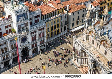 Venice, Italy - May 18, 2017: Piazza San Marco or St Mark`s Square with ancient Clock tower (Torre dell'Orologio) and Basilica di San Marco. This is the main square of Venice.