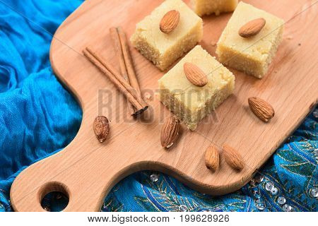 Halava Indian sweetmeats cut in squares decorated with almonds on wooden board on indigo cloth top view