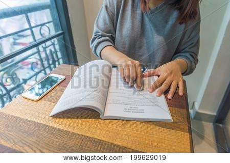 Young woman holding pencil and erase mistake on the notebook