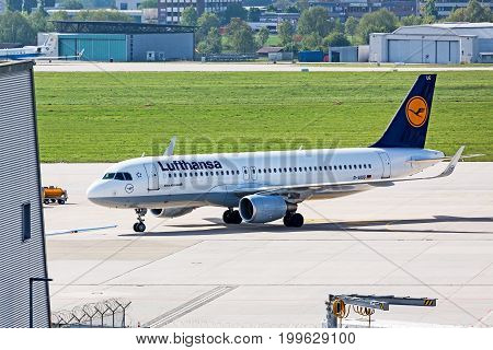 Stuttgart Germany - May 06 2017: Airbus A320 airplane from Lufthansa at ground (airport Stuttgart) on its way to parking position - green meadow and hangar in background
