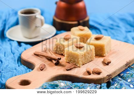 Flour halava squares with whole almonds served on indigo cloth with coffee and coffee maker. Indian sweetmeats closeup