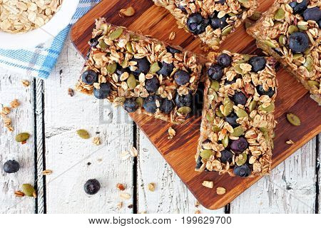 Superfood Breakfast Bars With Oats And Blueberries On Wood Board, Overhead Scene On Rustic Backgroun