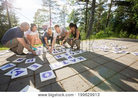 Business People Solving Crossword On Patio In Forest