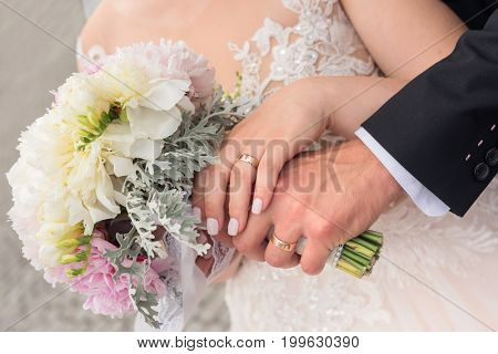 Hands of groom and bride with wedding bouquet.