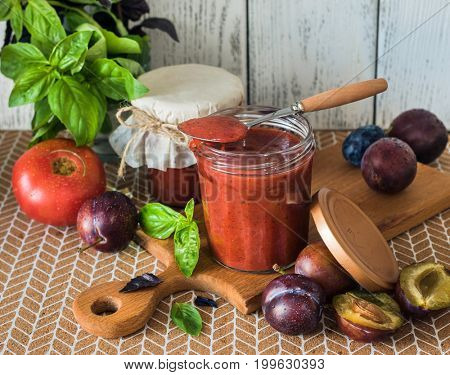 Plum sauce for meat dishes in glass jar.