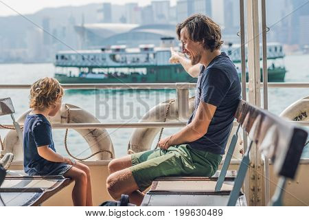 Father And Son Swim By Ferry Through Victoria Harbor In Hong Kong,china