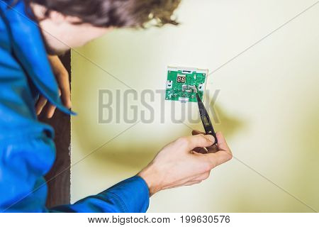 Electrician Installing An Electrical Thermostat In A New House