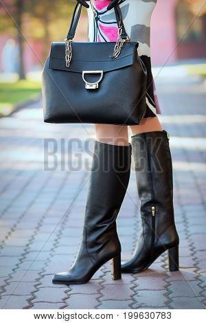 A girl in high-heeled boots with a bag in her hand