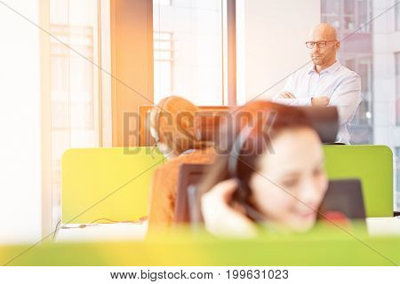 Mid adult businessman standing arms crossed with female colleagues working in foreground at office
