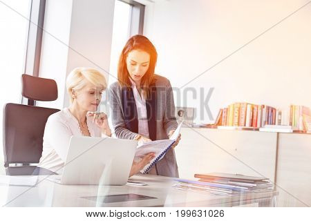 Businesswomen reading book at desk in office