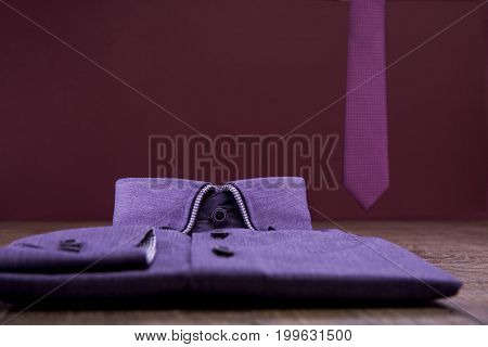 Lilac man's shirt and lilac ties on a wooden table. Background burgundy.