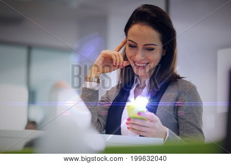 Smiling young businesswoman reading text message on smartphone at office