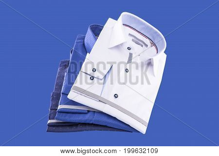 Men's shirts folded new: white blue and bright blue on a blue background.