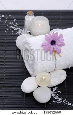 Spa setting with gerbera, candle, towel,salt, stones on mat