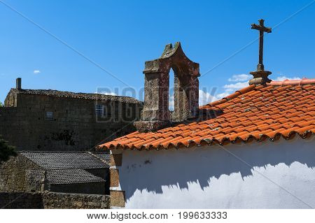 Detail of a cross and bell tower of a church in the historical village of Castelo Mendo in Portugal