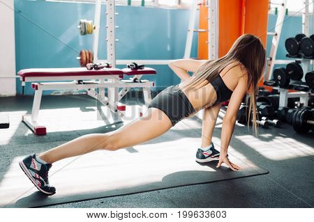 Fitness woman stretching full body over gym background