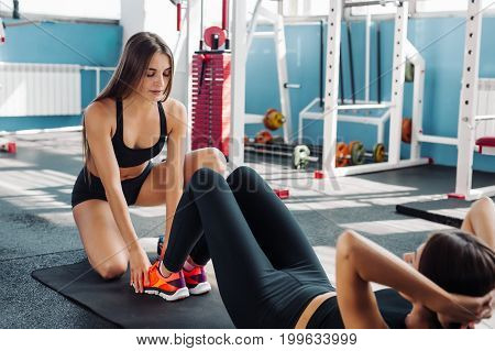 Teen girl working out in the gym coach
