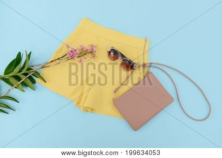 Summer yellow shorts ,sunglasses and lilac flowers ,bag on blue background .
