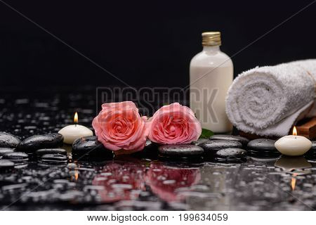 Two pink rose with candle ,towel, bottle oil  and therapy stones