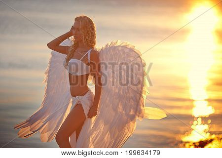 Fine art photo of a woman in white dress as an angel