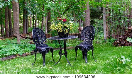 Seating for two at the edge of a lush green forest at a bistro set.
