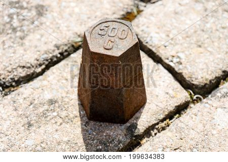 copper weight mass on floor in daylight on concrete floor