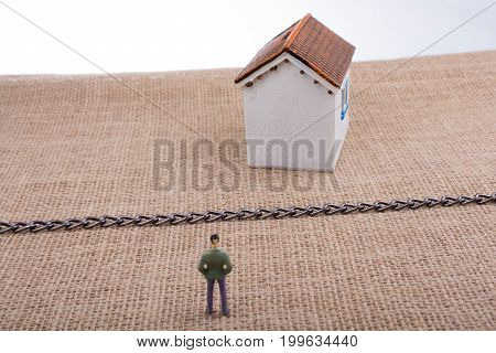 Man Figurine And A Model House Beyond The Chain