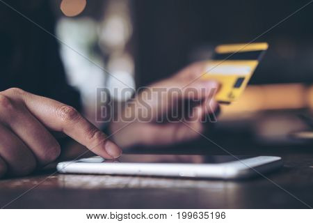 Closeup image of a woman's hand holding credit card and pressing at mobile phone on wooden table in office