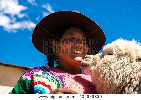 Peruvian woman holding her Alpaca