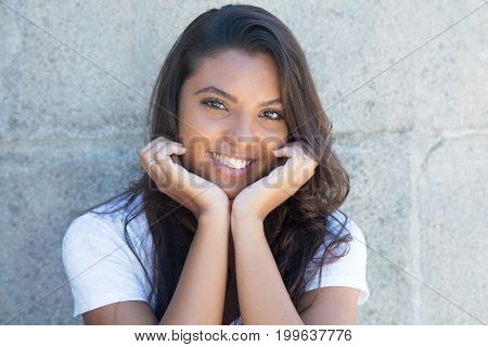 Laughing latin american woman with long hair outdoor in the summer
