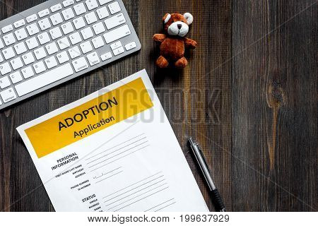 Adoption application on wooden table background top view.
