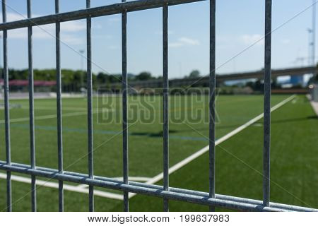 football soccer field viewed through gate fence with field lines