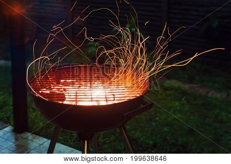 Burning coals and sparks coming out of the barbecue. BBQ brazier with sparks