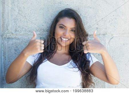 Latin american woman with long hair showing both thumbs up outdoor in the summer