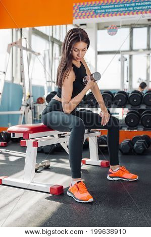 Fit young woman 20s doing shoulder raises with dumbbells in gym 20s
