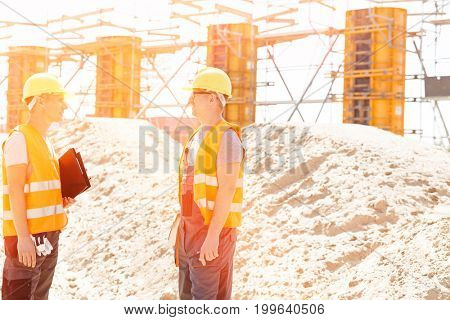 Side view of supervisors discussing at construction site