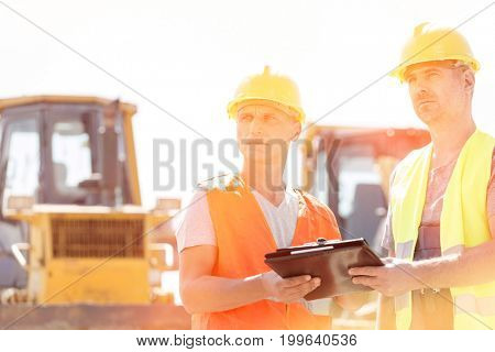 Engineers looking away while holding clipboard at construction site against clear sky