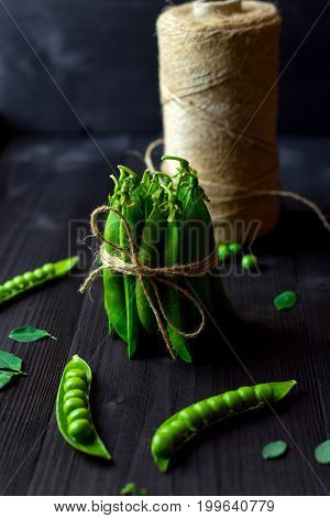 Bunch Of Fresh Mature Pods Of Green Peas Tied With A Rope On Black Wooden Background. Bio Healthy Fo