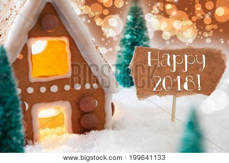 Gingerbread House In Snowy Scenery As Christmas Decoration. Christmas Trees And Candlelight. Bronze And Orange Background With Bokeh Effect. English Text Happy 2018 For Happy New Year