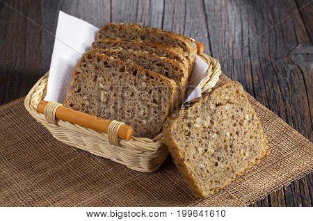 Bread slices with different seeds in basket on dark wooden table