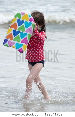 View of Girl coming out of the ocean waves with a boogy board