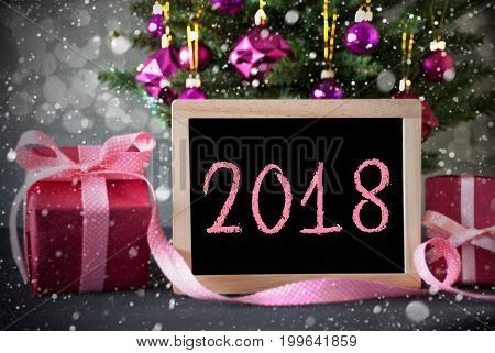 Christmas Tree With Rose Quartz Balls, Snowflakes And Bokeh Effect. Gifts Or Presents In The Front Of Cement Background. Chalkboard With English Text 2018 For Happy New Year